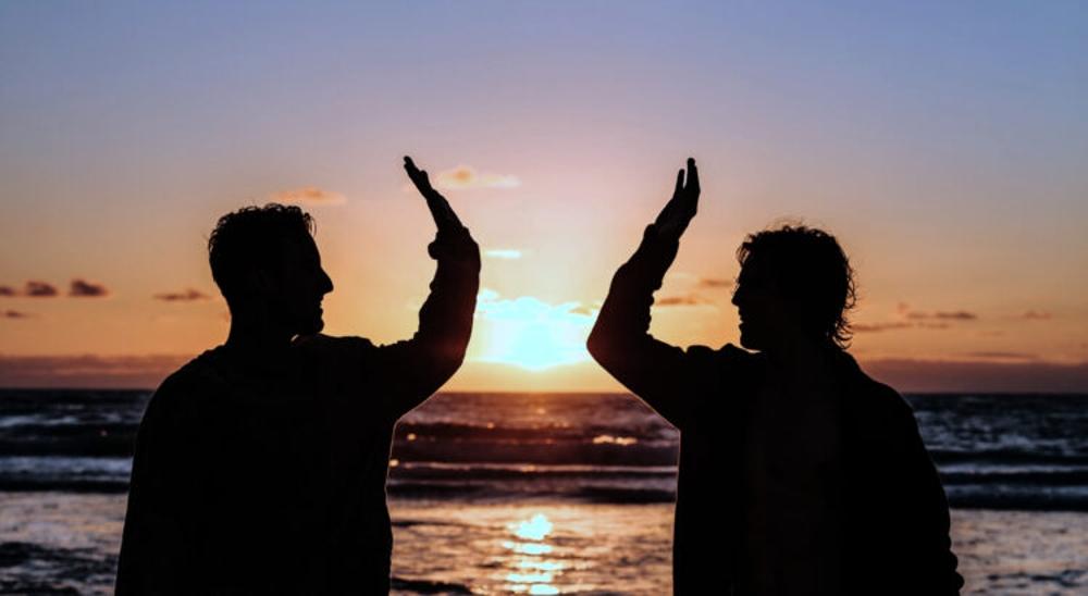 High five oder Tschüss symbolisiert durch zwei Männer mit ausgestrecktem, angewinkeltem Arm